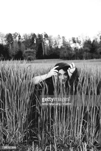 Woman With Hand In Hair While Sitting Amidst Grass