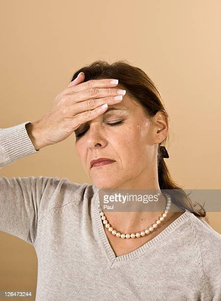 Woman with hand on forehead
