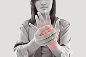 Asian woman suffering from pain in bone against gray background, Concept with hand arthritis grimace in pain