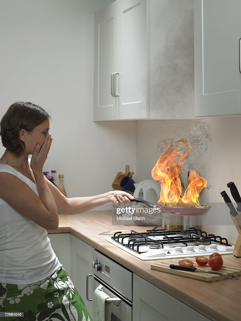 'Woman with hand to face holding burning frying pan in domestic kitchen, side view'