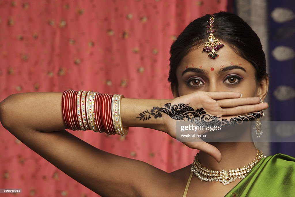 woman with hands decorated in henna, standing against wall of sari fabric : Stock Photo