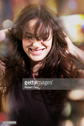 Woman with hands in hair laughing : Stock Photo