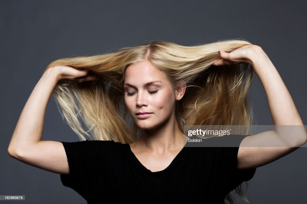 woman with hands in her hair, studio background