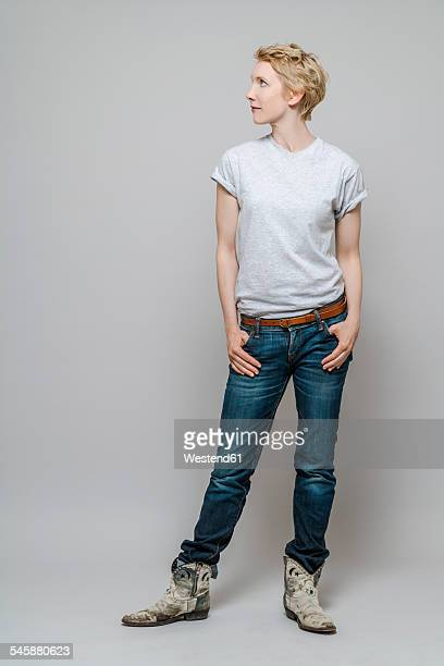 Woman with hands in her pockets watching something in front of grey background