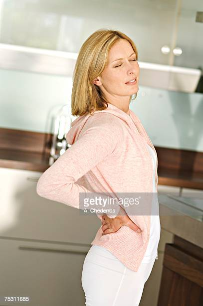 Woman with hands on her back, eyes closed