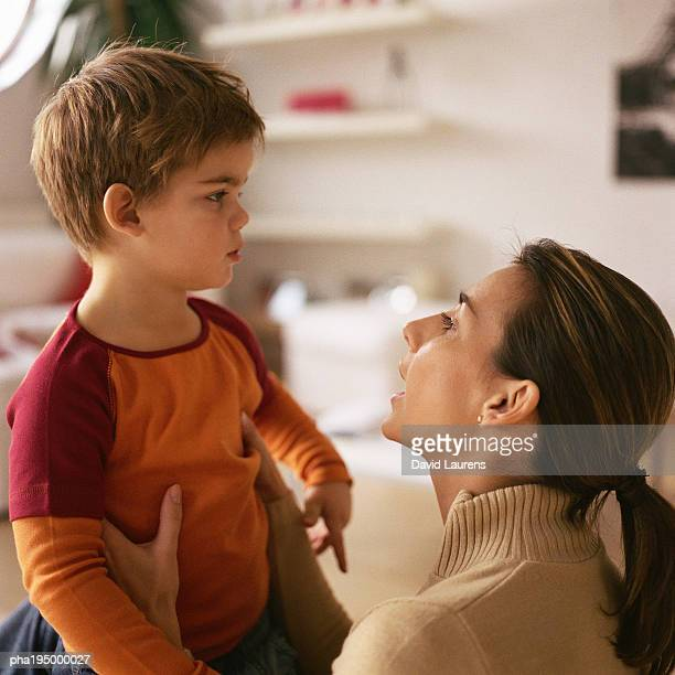 Woman with hands on little boy's sides, talking to him.