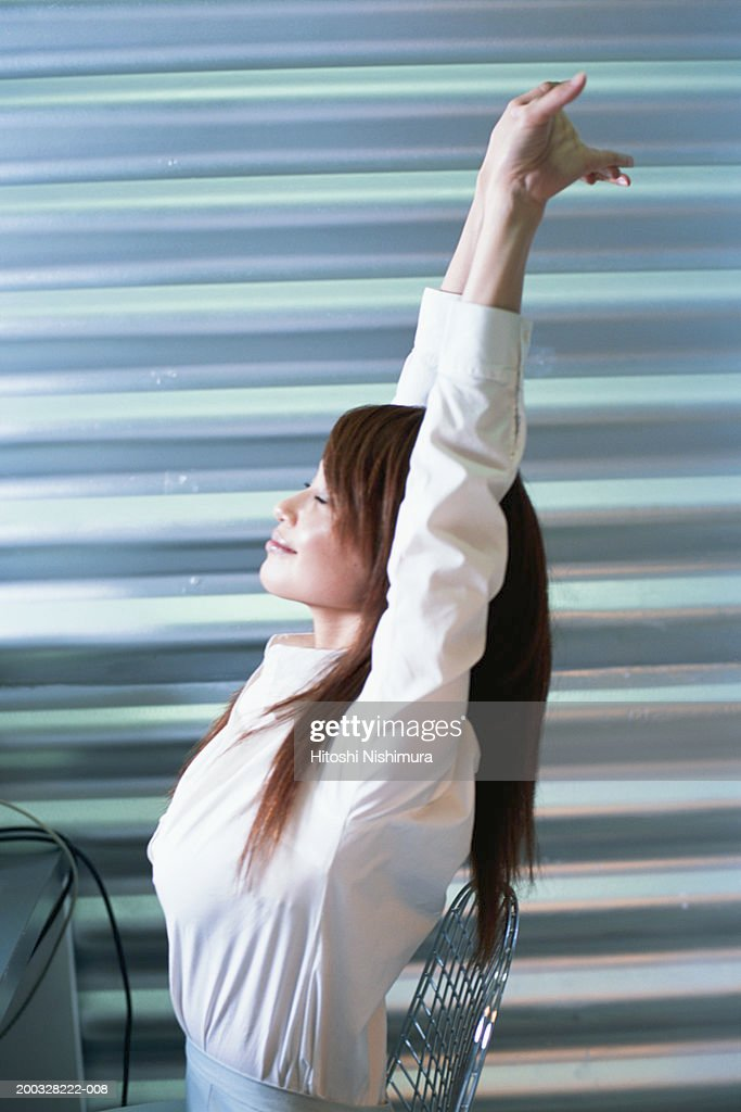 Woman with hands raised, eyes closed, side view : Stock Photo