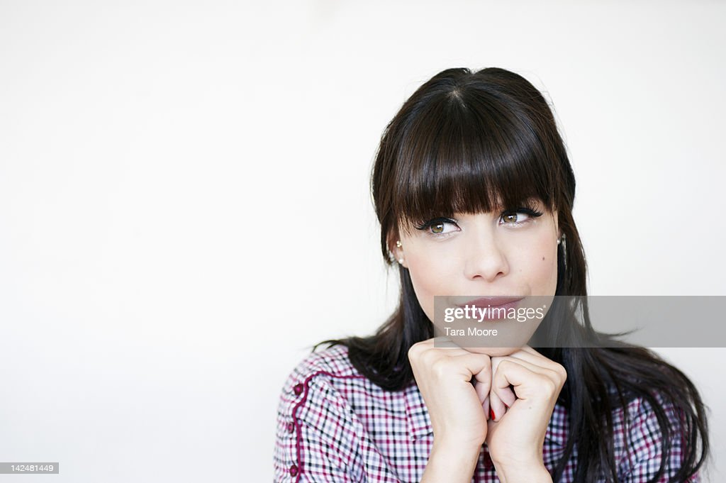 woman with hands under chin looking to the side : Stock Photo