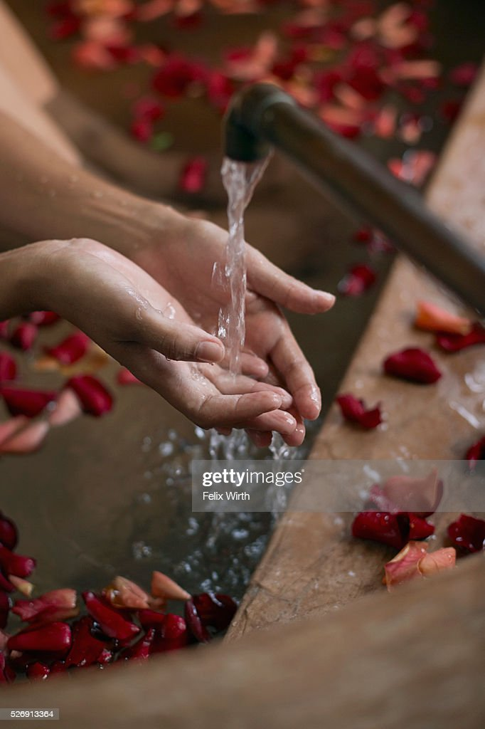 Woman with hands under faucet : Stock Photo