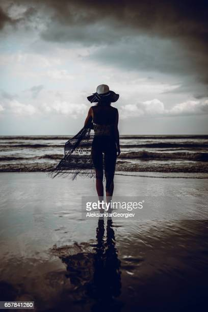 Woman with Hat and Sundress Goes Toward Stormy Ocean