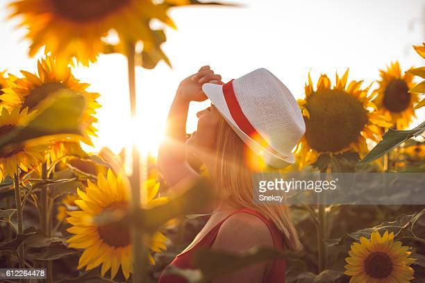 Woman With Hat in a Sunflower Field