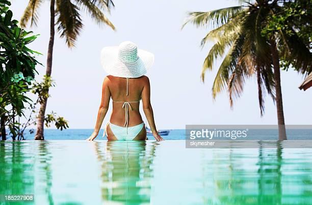 Woman with hat sitting on the edge of  swimming pool.