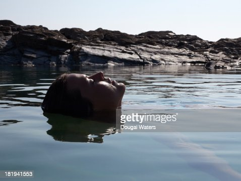 Woman with head back and eyes closed in rock pool.