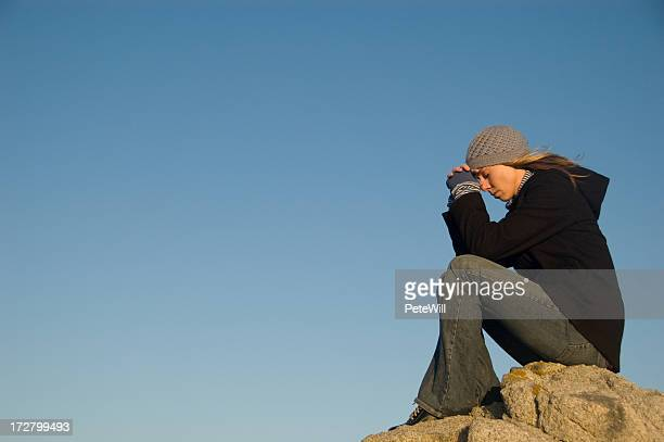 Woman with head on clasped hands praying on a rock outside