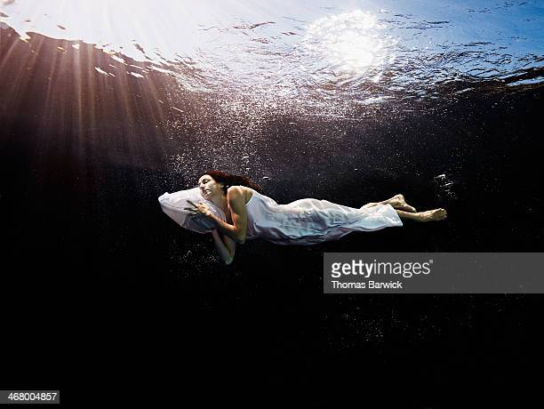 Woman with head on pillow sleeping underwater