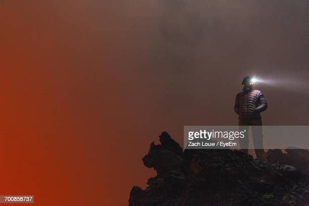 Woman With Head Torch Standing Against Orange Sky