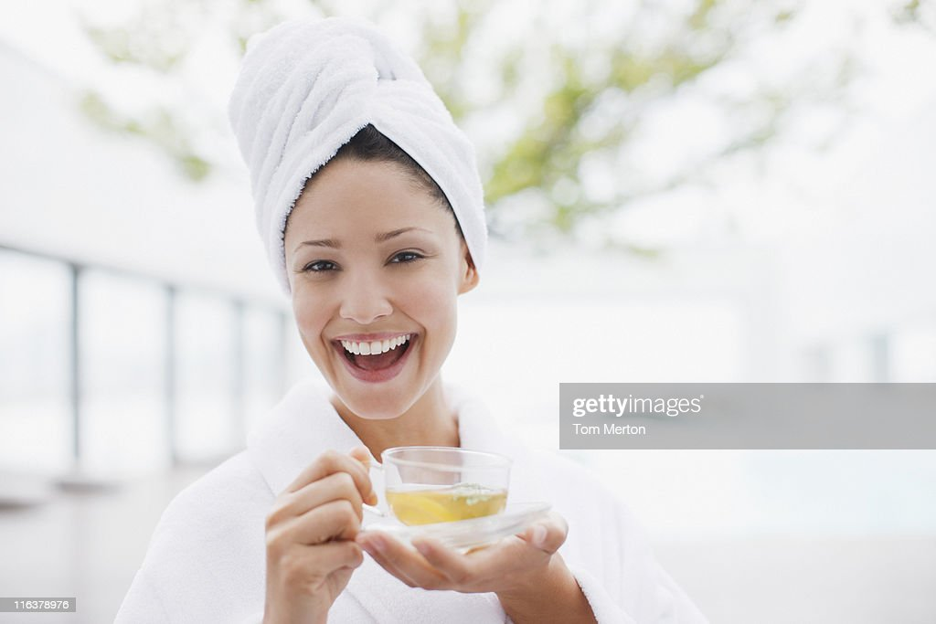 Woman with head wrapped in towel drinking tea : Stock Photo