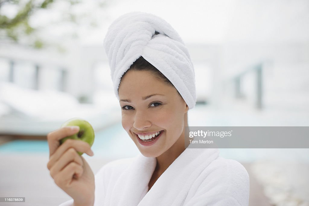 Woman with head wrapped in towel eating apple at poolside : Stock Photo