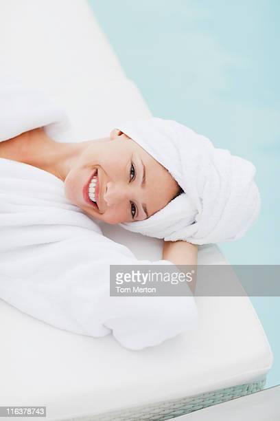 Femme avec tête enveloppé dans une serviette Allongez-vous au bord de la piscine
