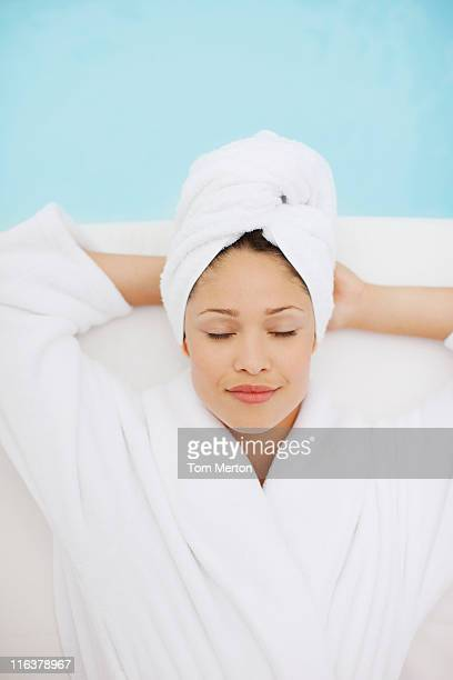Woman with head wrapped in towel laying at poolside