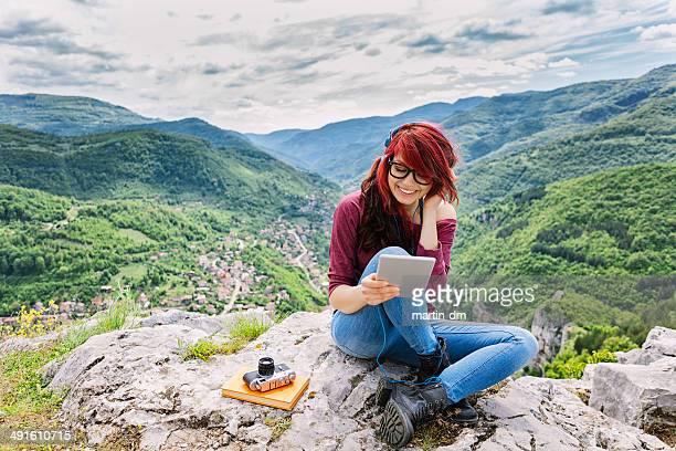 Frau mit Kopfhörer und tablet PC auf die Berge