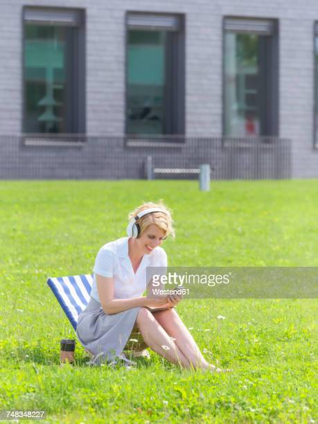 Woman with headphones sitting on a meadow looking at cell phone