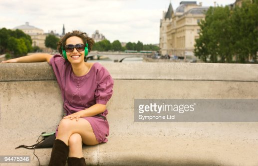 Woman with headphones sitting on bench : Foto stock
