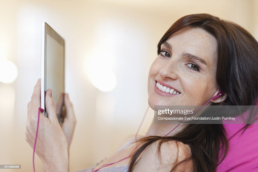 Woman with headphones using digital tablet : Stock Photo