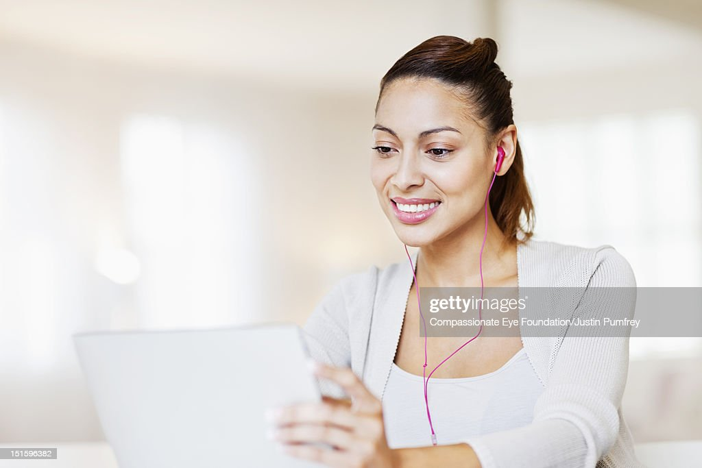 Woman with headphones using laptop : Stock Photo