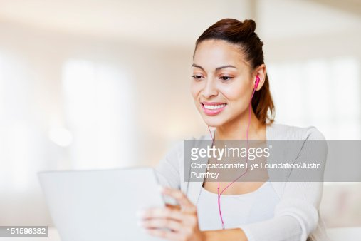 Woman with headphones using laptop : Stock Photo