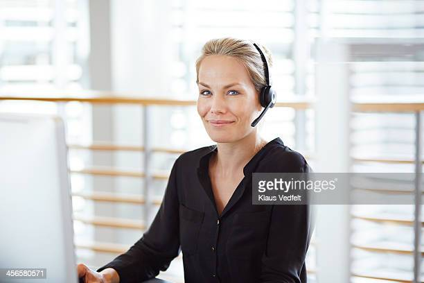 Woman with headset smiling to camera