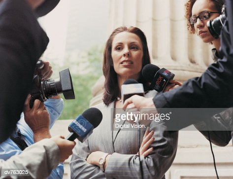 Woman With Her Arms Crossed Being Interview and Photographed by Journalists : Stock Photo