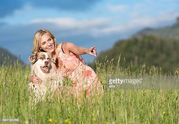 Mujer con su perro pastor australiano en naturaleza