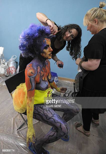 A woman with her body painted is prepared during a body painting happening on July 18 2009 at Ramblas in the centre of Barcelona AFP PHOTO/LLUIS GENE