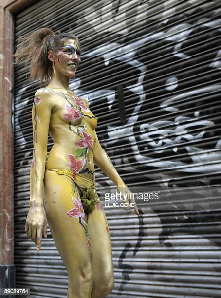 A woman with her body painted walks through the streets during a body painting happening on July 18 2009 at Ramblas in the centre of Barcelona AFP...