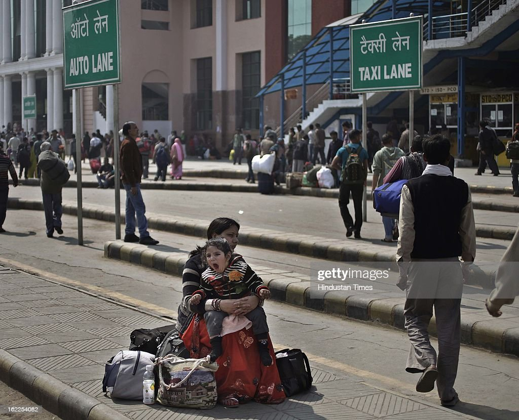 A woman with her child and their baggage's at New Delhi Railway station during the second day of a nationwide strike called by trade unions on February 21, 2013 in New Delhi, India.