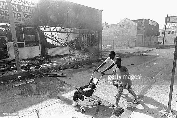 A woman with her children walk past several burn out businesses on South Vermont Ave in South Central Los Angeles Los Angeles has undergone several...