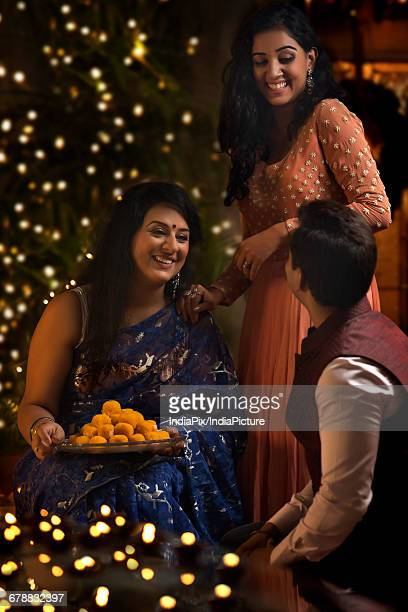 woman with her daughter and son-in-law celebrating diwali
