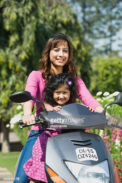 Woman with her daughter riding a scooter in a park