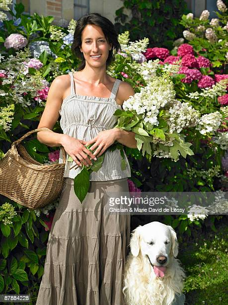 Woman with her dog,  holding flowers