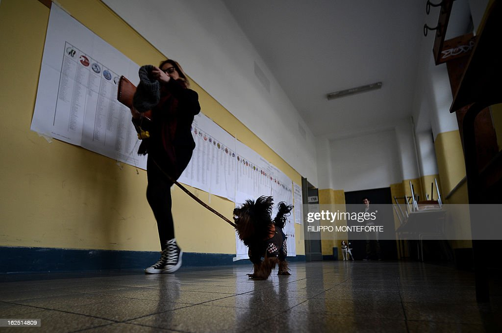 A woman with her dogs in a polling station in the center of Rome on February 24,2013 during Italy's general elections. Italians fed up with austerity voted on February 24 in the country's most important election in a generation, as Europe held its breath for signs of fresh instability in the eurozone's third economy.