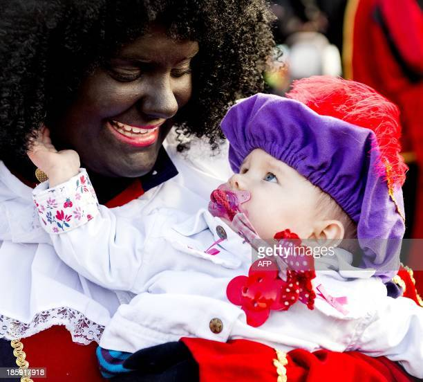 A woman with her face painted black holds a baby as a few hundred people some of them dressed up as Zwarte Piet take part in a demonstration in favor...