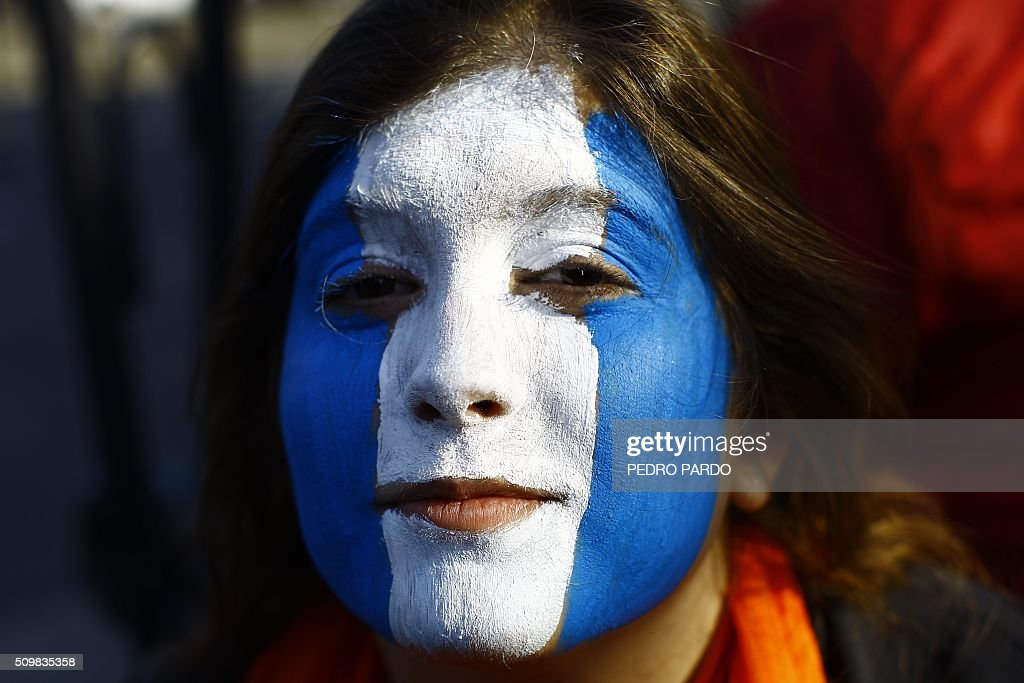 A woman with her face painted waits for Pope Francis to arrive in Mexico City on February 12, 2016. Pope Francis will arrive in Mexico on Friday, where he will visit until February 17. AFP PHOTO/ Pedro PARDO / AFP / Pedro PARDO