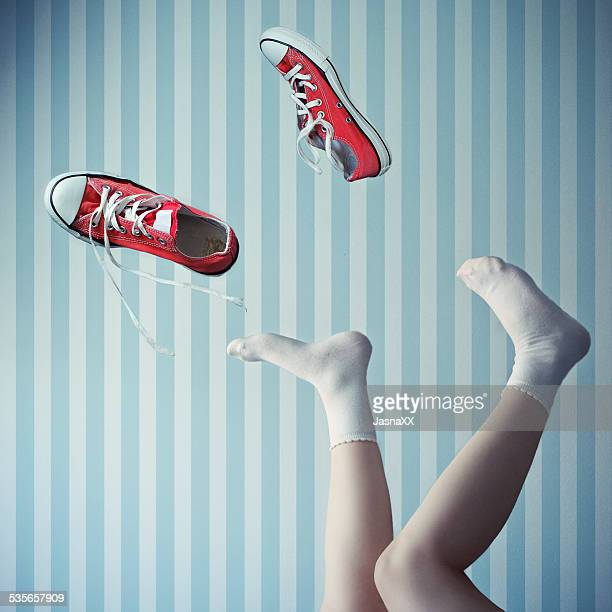 Woman with her legs in the air with trainers mid air