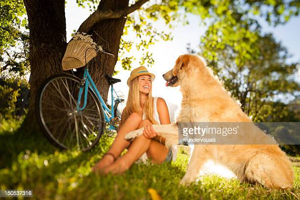 Woman With Her Pet Dog Sitting On Grass