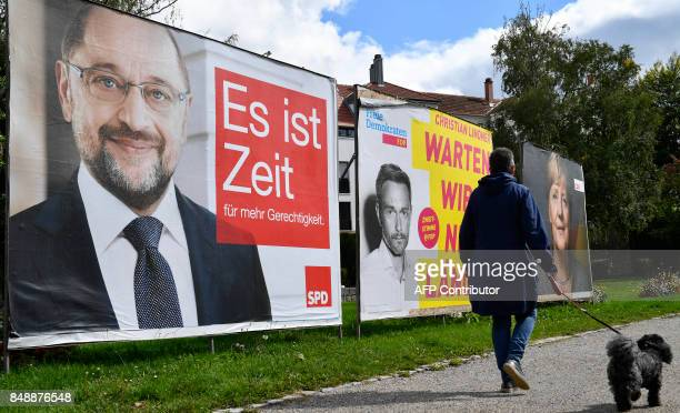 A woman with her poodle walks past election billboards featuring the top candidates in the upcoming parliamentary elections of the Social Democratic...