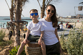 Woman with her son in white T-shirts standing on the beach.