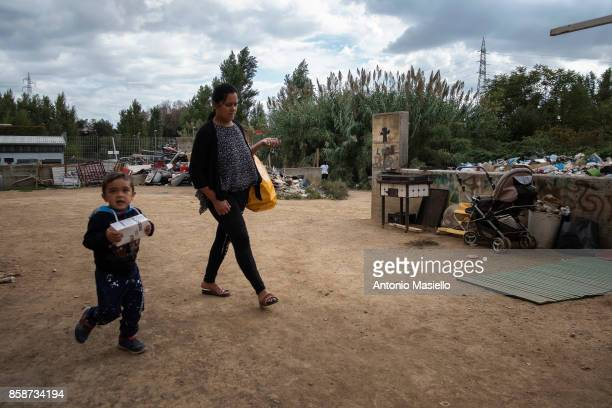 A woman with her son walk outside an occupied building on October 4 2017 in Rome Italy Since 5 years hundreds of people including Italians Roma...