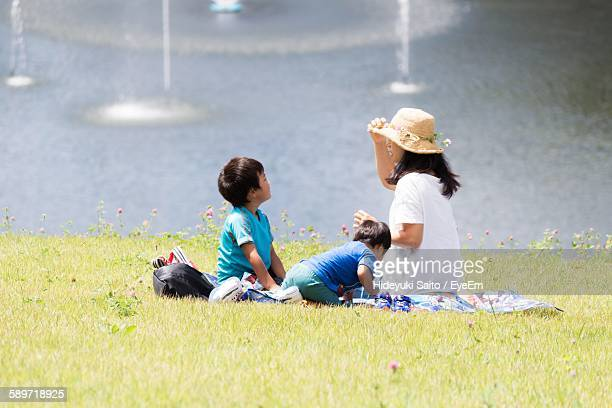 Woman With Her Sons Sitting On Field By Lake