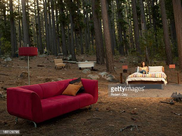 A woman with home furnishings laying on bed outdoors in the woods